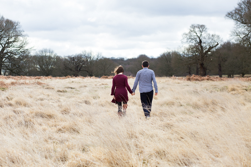 Man and lady walking through long grass.