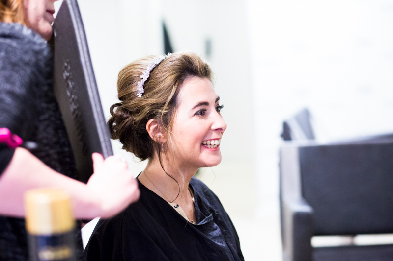 Lady laughing while having her hair done.