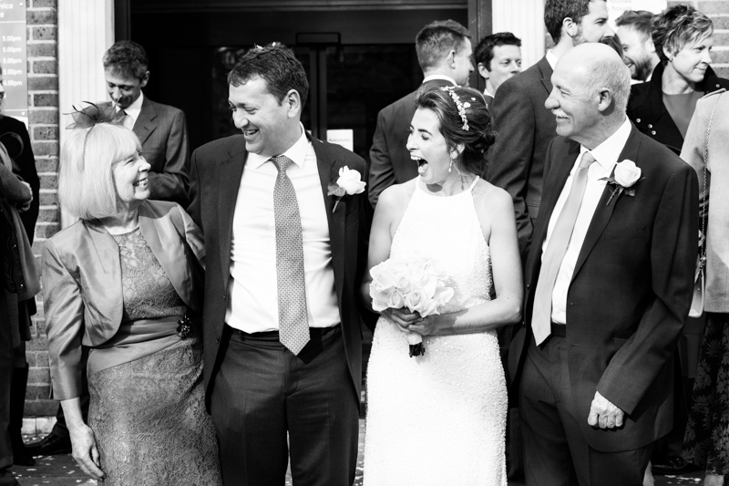 Bride and groom laughing with parents.