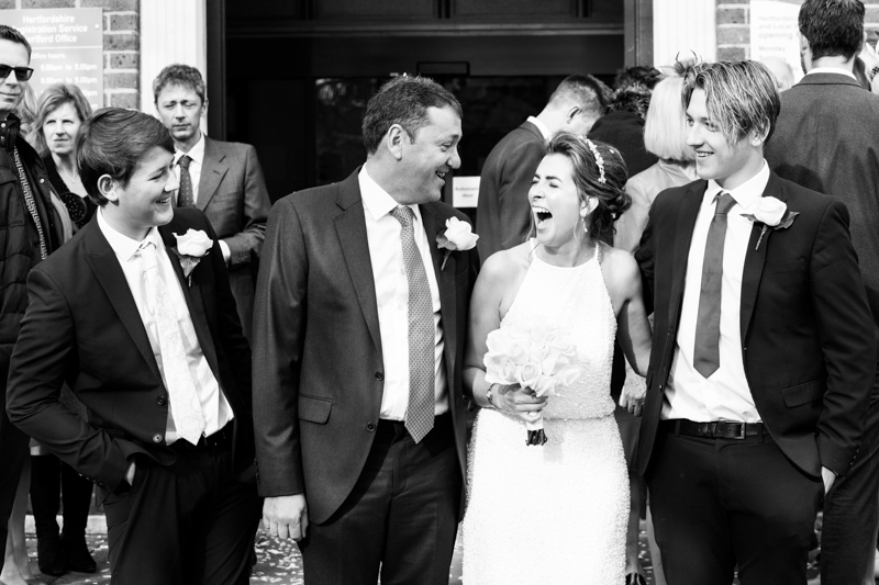 Bride and groom laughing with friends.