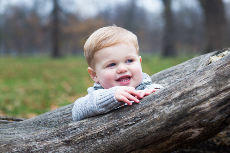 Little boy smiling while leaning on a tree trunk.