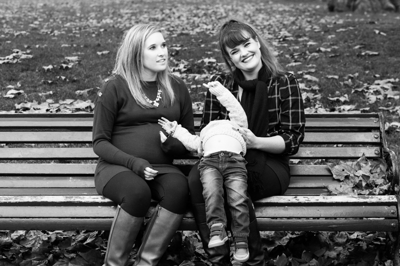 Two sisters sitting on a bench with a little boy, who's thrown his head backwards.