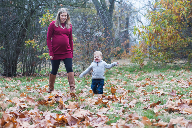 Pregnant lady watching her son playing in the autumn leaves.