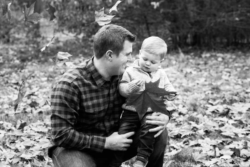 Dad hugging his son while he looks at a large autumn leaf.