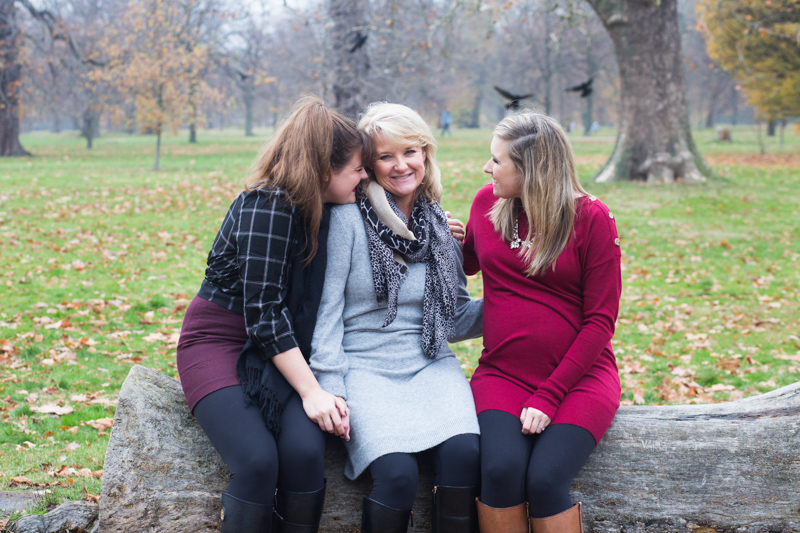 Two girls cuddling their mother while sitting on a tree trunk in the park.