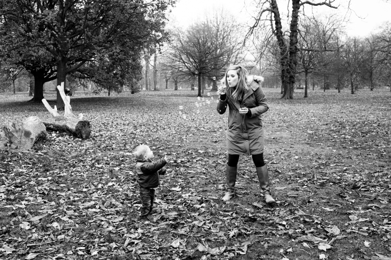Lady blowing bubbles for her son in the park.