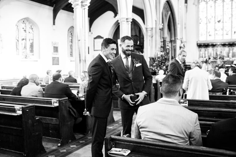 Two men laughing in a church.