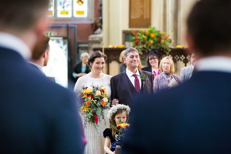 Bride walking in the church service with her father and bridesmaid.