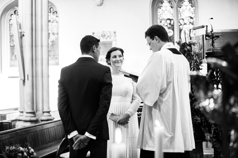 Bride and groom in church with vicar.