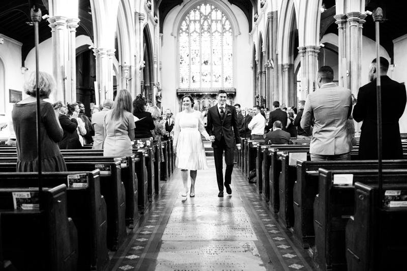 Bride and groom walking down aisle of church.