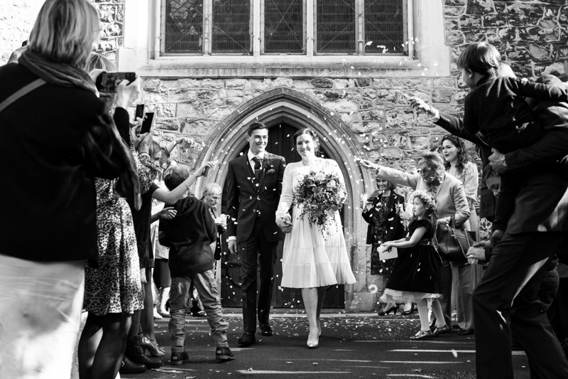 Newly weds walking away from church with confetti being thrown on them.