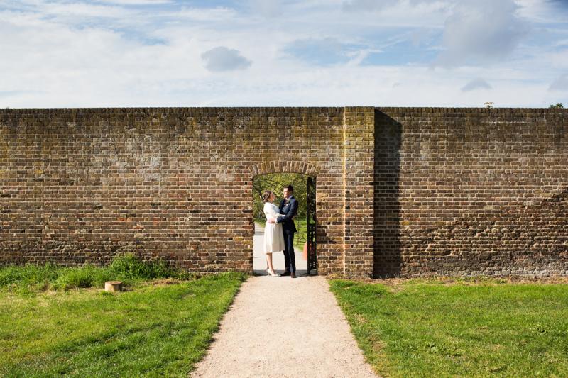 Wedding couple in doorway of brick wall.