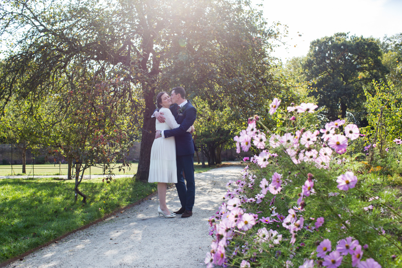 Bride and groom hugging next to some pink flowers.