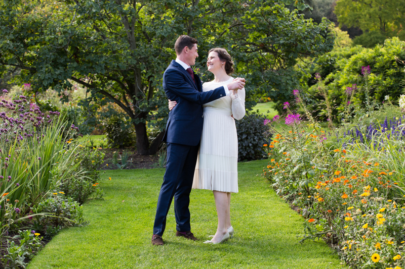 Newly wedded couple dancing surrounded by flowers.