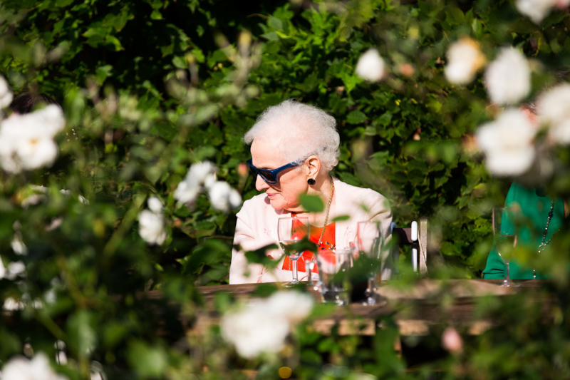 Lady with sunglasses sitting behind white roses.