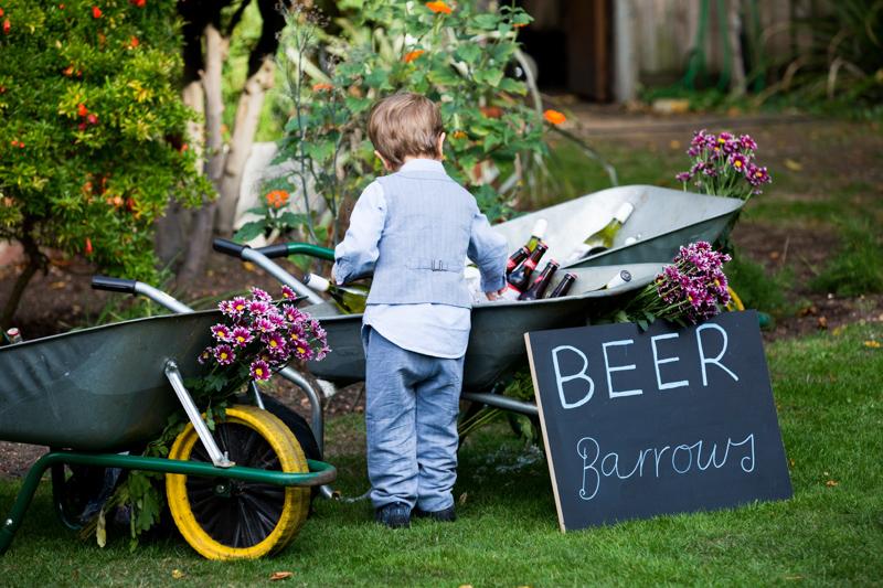 Boy looking into wheelbarrows full of beer.