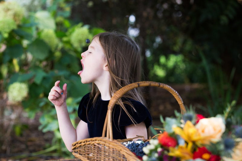 Girl throwing blueberry into her mouth.