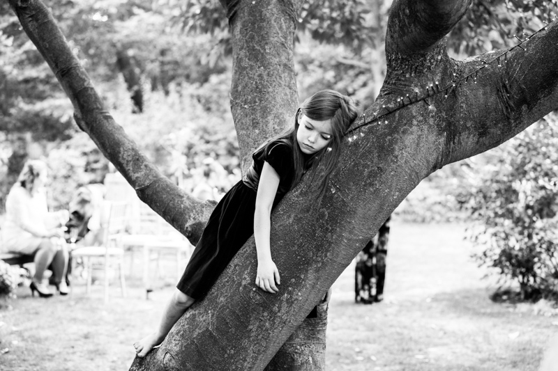 Tired looking girl lying on branch of tree.