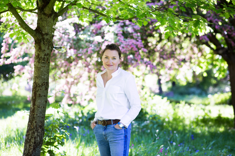 Lady smiling in front of pink blossom trees.