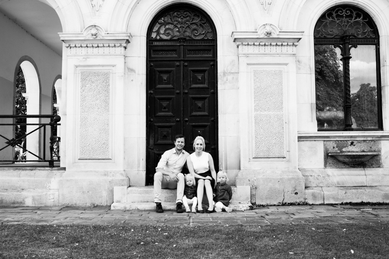 Family of four sitting on a step in front of beautiful building.