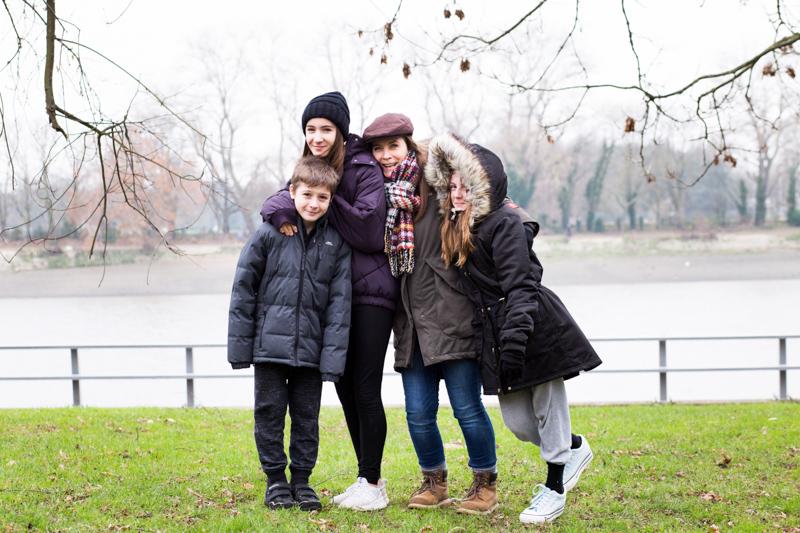 Mum and three children standing on grass.