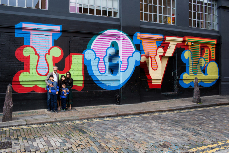 family standing in front of a wall with LOVE written in huge writing.