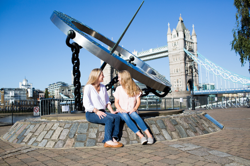 Mum and daughter sitting in front of Tower Bridge.