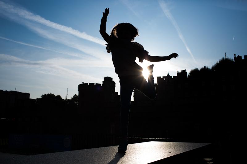 Silhouette of girl dancing in front of Tower Bridge.