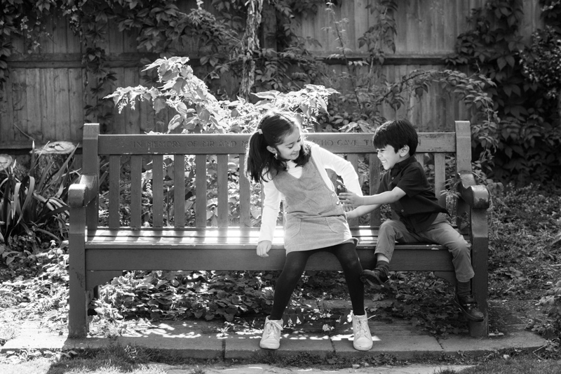 Brother and sister play fighting on a bench.