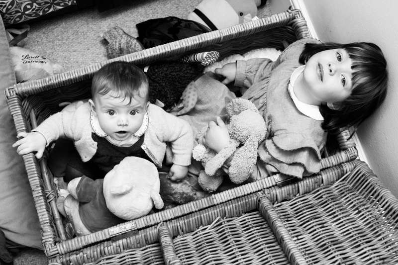 Little girl and baby sitting in a box looking up.