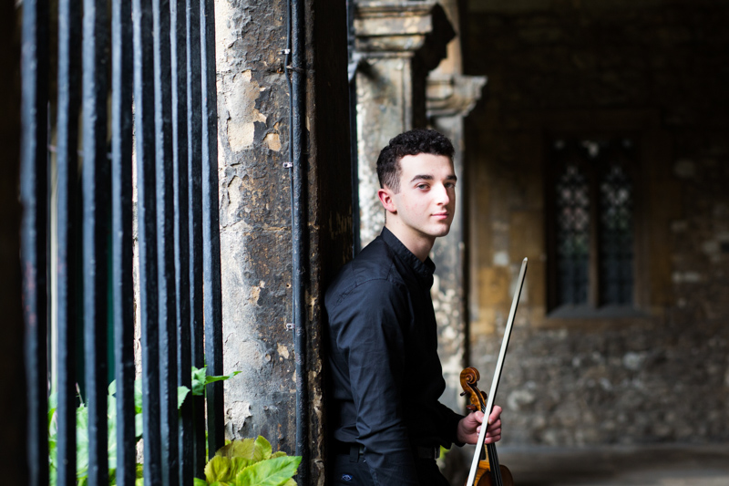 Man leaning against wall holding a violin and bow.