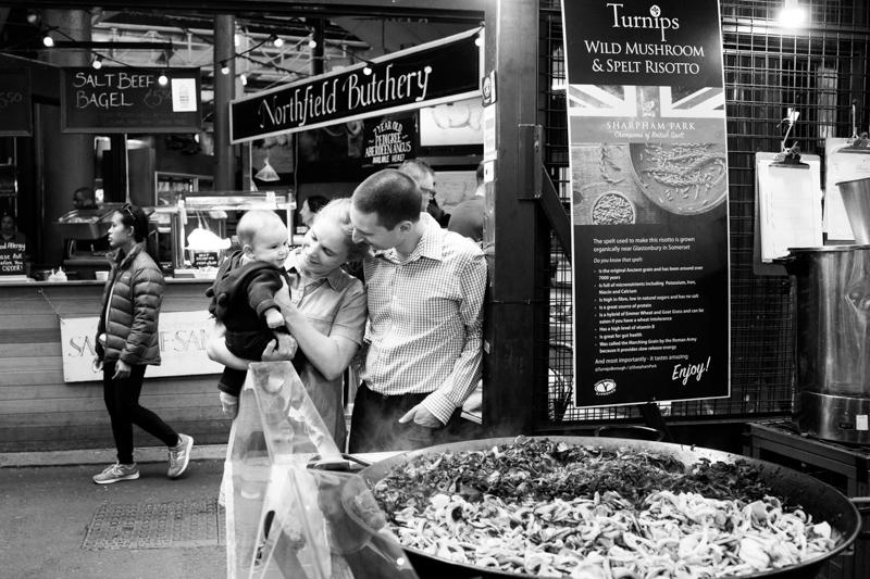 Mum, dad and baby standing behind huge pan of cooking food.