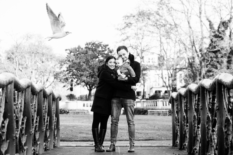 man, lady and baby standing on a bridge with a seagull about the fly past them.