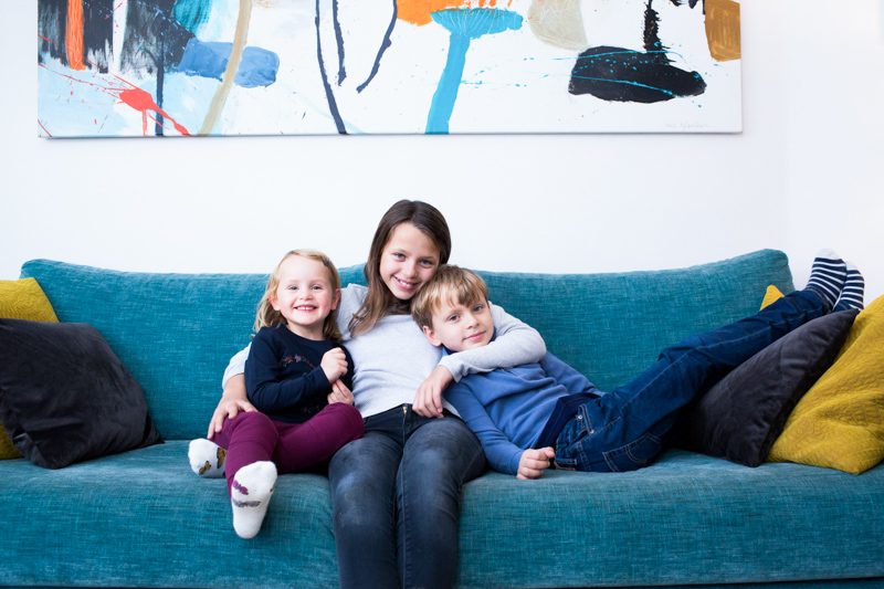 relaxed family portraits - three children sitting on a blue sofa