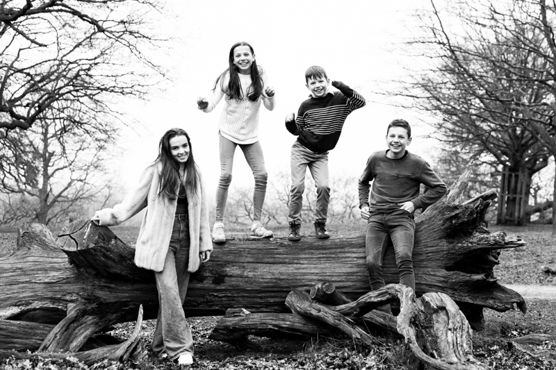 Four children having fun by a huge tree trunk