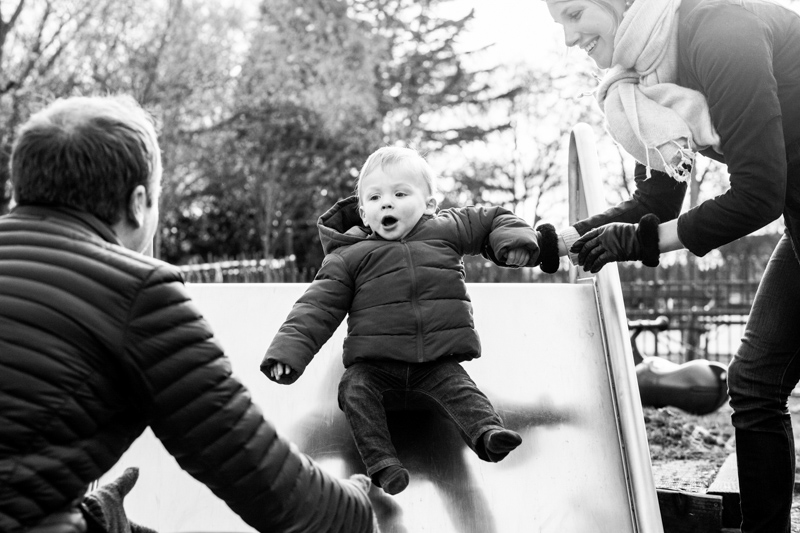 Baby on a slide with two grown ups