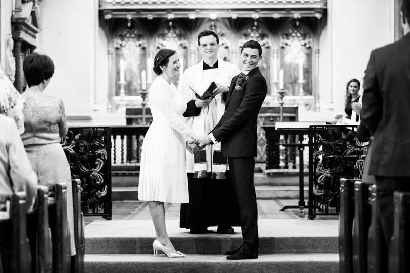 Bride and groom smiling in front of vicar