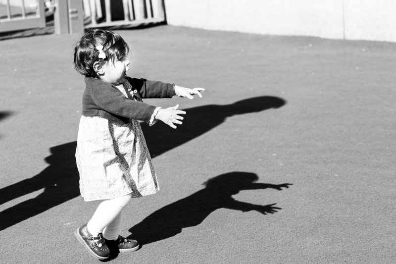 little girl walking with her arms stretched out