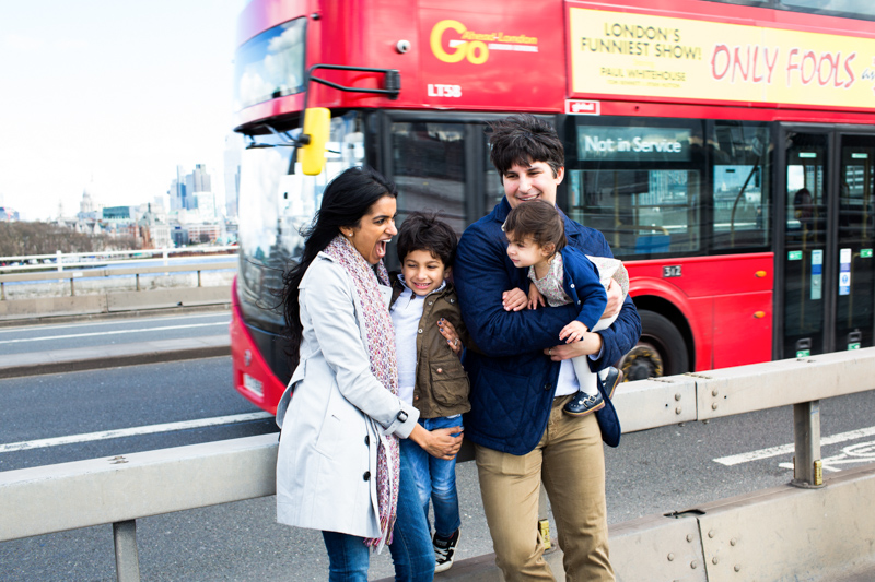 family of four laughing in front of red London bus