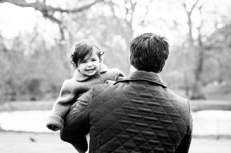 natural portrait of a little girl held by a man
