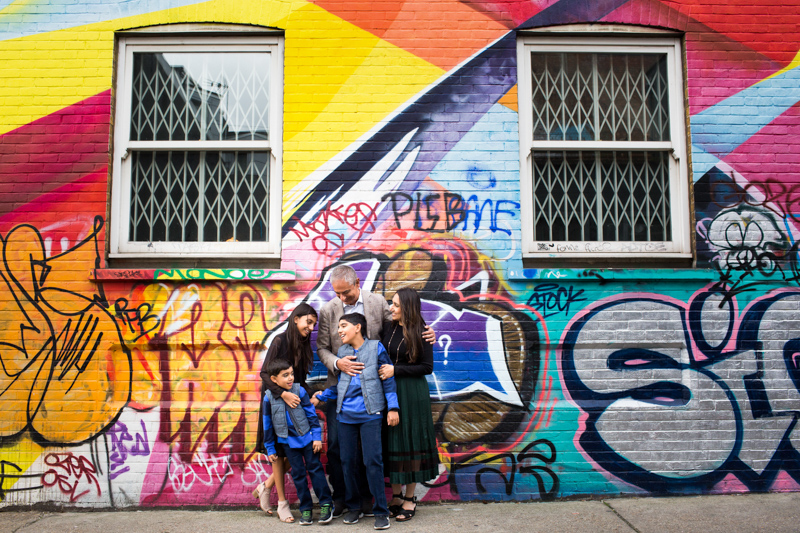 family of five standing in front of a colourful wall