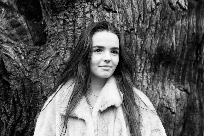 Girl with long hair leaning against a tree