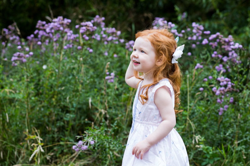 little girl with red hair and white dress in front of purple flowers