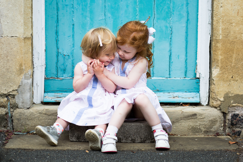 Two sisters in white dresses hugging in front of blue door.