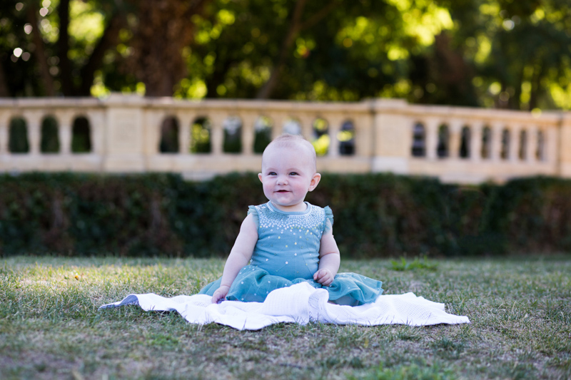 baby sitting on a white blanket on the grass