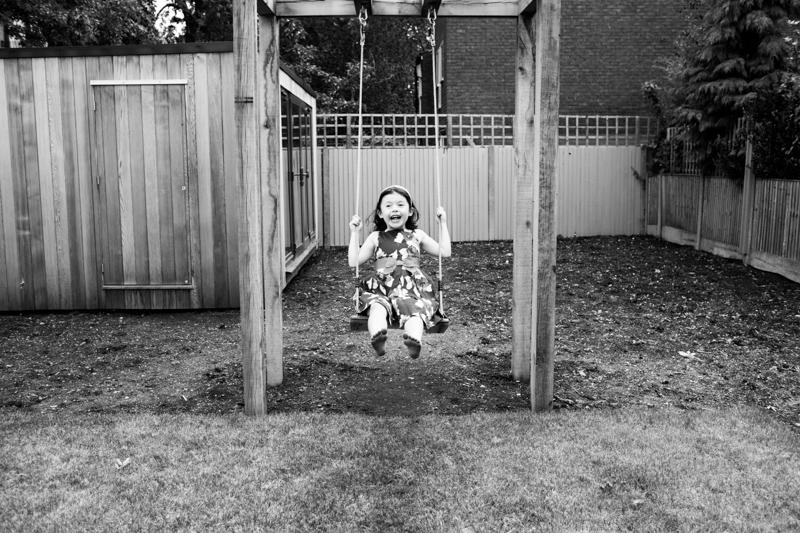 Little girl swinging on a swing in a garden.