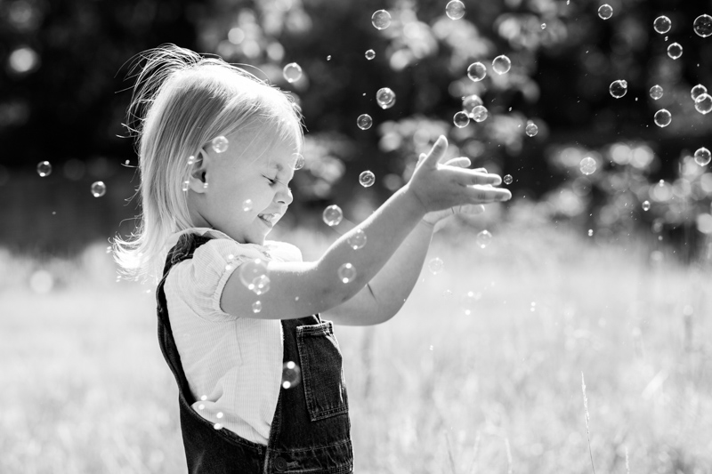 girl with eyes closed playing with bubbles