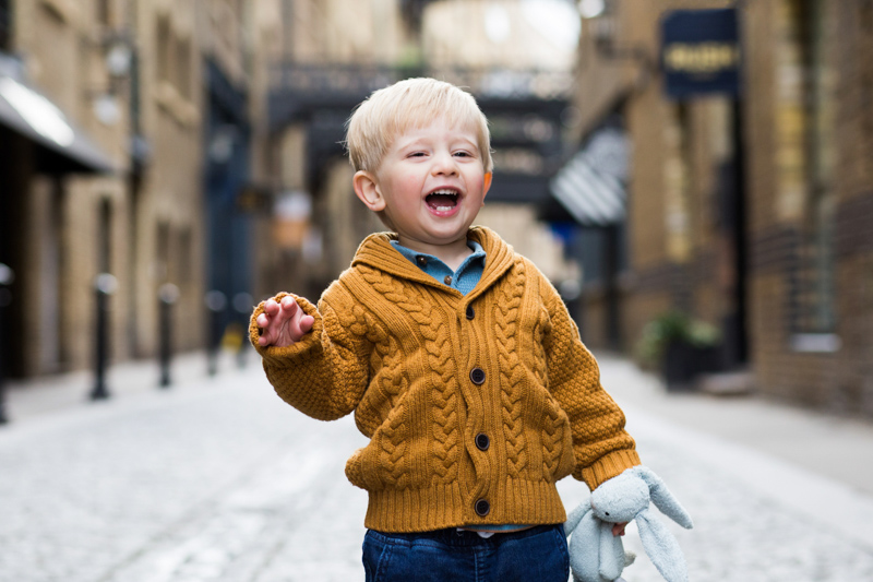 little boy holding his toy rabbit and laughing
