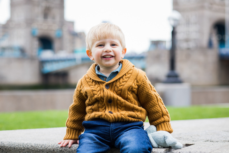 Boy sitting smiling with Tower Bridge in the background.