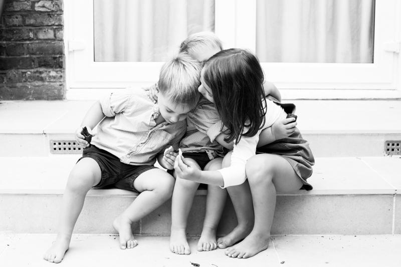 Three siblings cuddling on a step.